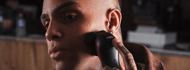 hombre usando una máquina de afeitar rotativas power series remington