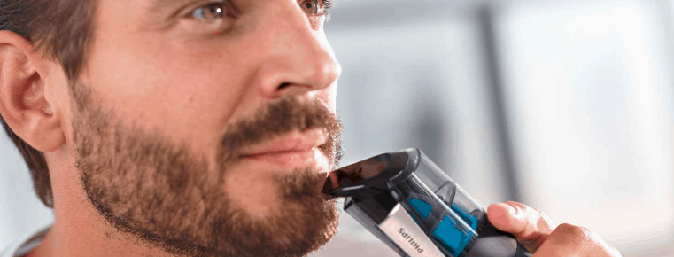 hombre usando una máquina de afeitar con aspiración de pelos