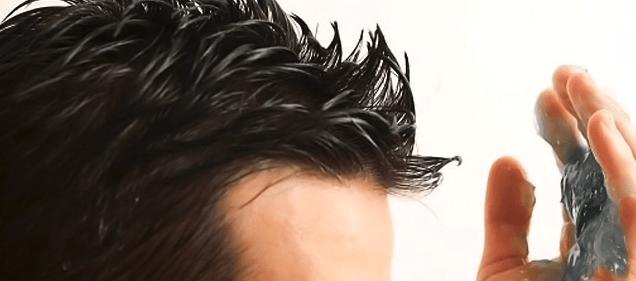 hombre poniéndose producto fijador en el pelo